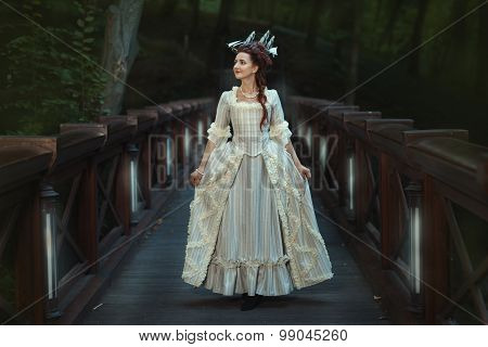 The Girl In An Old Ball Dress Walking On Bridge.