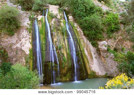 Unusual waterfall. Three parallel stream running down the steep slope and fall into the oval pool