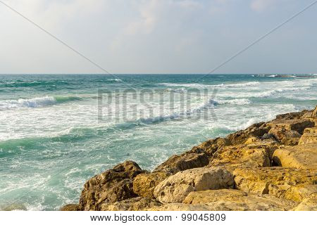 Waves of the Mediterranean sea beating against the stony shore