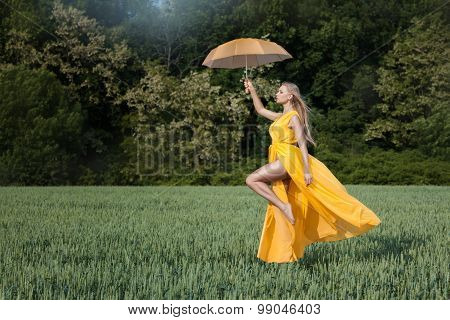 Girl Flies Over The Field. In His Hand Umbrella.