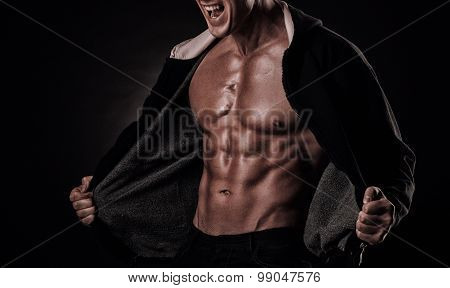 Portrait Of Screaming Bodybuilder With Tight Muscles And His Mouth Open On A Black Background.
