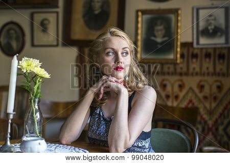 Young beautiful blond woman with sad eyes sitting in a retro atmosphere.