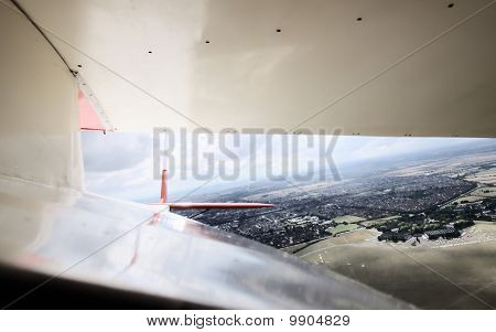 In flight view back under the wing from open cockpit of vintage Slingsby T-21 glider.