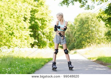 fitness, sport, summer, rollerblading and healthy lifestyle concept - happy young woman in roller skates and protective gear riding outdoors