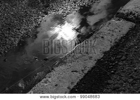 Sunshine Reflecting From A Puddle Of Rain Water In A Road