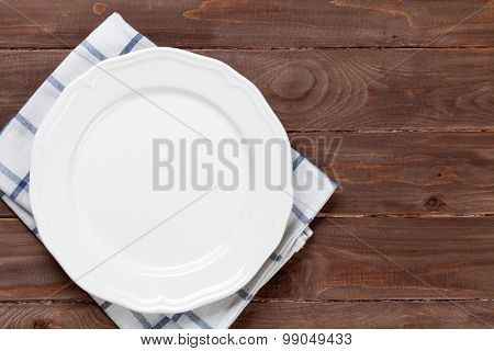 Empty plate over wooden table background. View from above with copy space