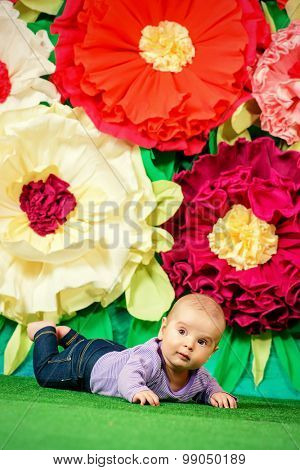 Portrait of a cute little baby  among huge bright flowers. Happy childhood.