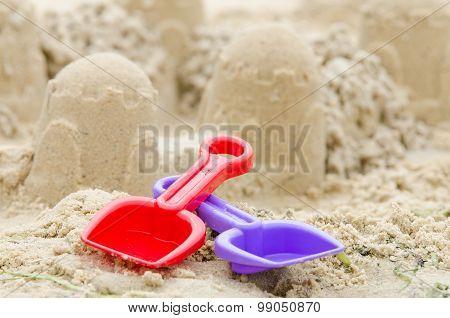 Shovel And Rake On The Background Of Sand Castle