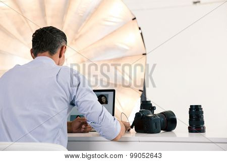 Back view portrait of photographer using laptop at his workplace
