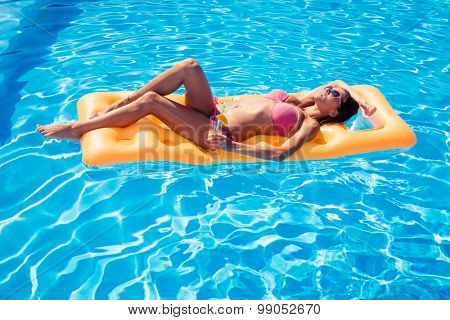 Beautiful girl sunbathing on air mattress in the swimming pool