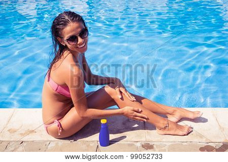 Happy woman sitting near swim pool and applying sun cream outdoors