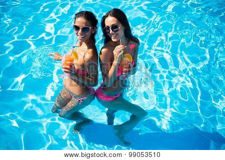 Portrait of a two happy girls drinking cocktails in swimming pool