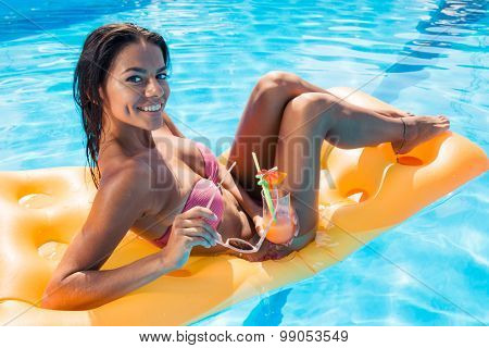 Portrait of a happy beautiful girl lying on air mattress in swimming pool