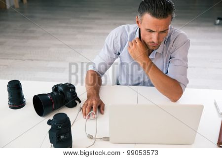 Portrait of a photographer using laptop at his workplace