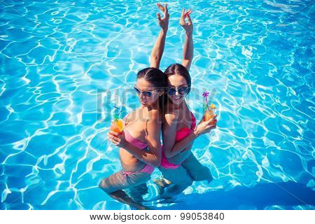 Portrait of a two attractive girls drinking cocktails in swimming pool