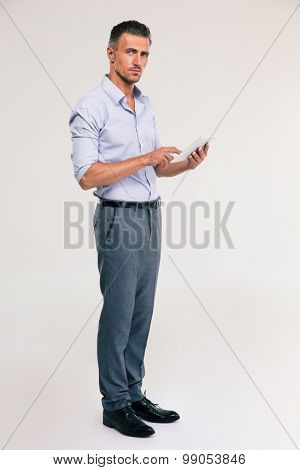 Full length portrait of a handsome man using tablet computer isolated on a white background. Looking at camera