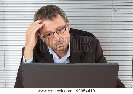 Handsome Serious Unshaven  Man Sitting Looking Directly At His Computer