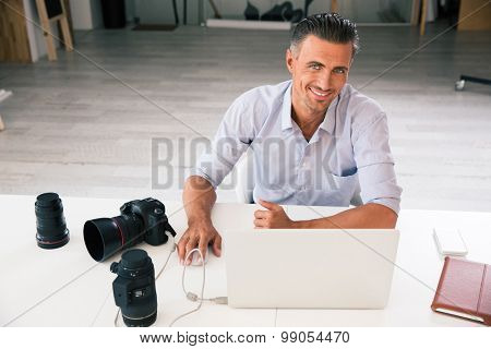 Portrait of a happy photographer using laptop at his workplace and looking at camera