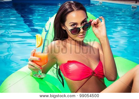 Beautiful girl lying on air mattress with cocktail in the swimming pool