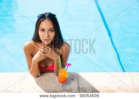 Portrait of attractive young woman standing in swim pool outdoors