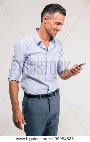 Portrait of a smiling businessman using smartphone isolated on a white background