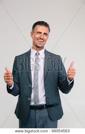 Portrait of a smiling businessman showing thumbs up isolated on a white background