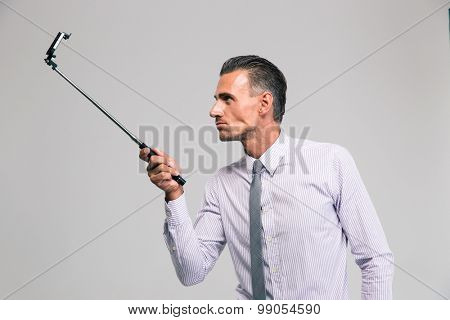 Portrait of a handsome businessman holding selfie stick isolated on a white background