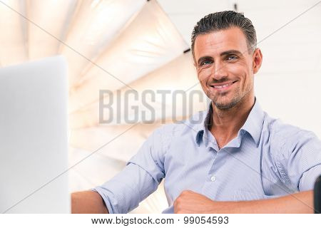 Happy confident man using laptop and looking at camera in studio