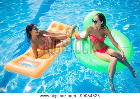 Portrait of a two attractive girlfriends sunbathing on air mattress and drinking cocktails in swimming pool