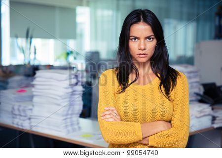 Portrait of angry businesswoman standing with arms folded in office