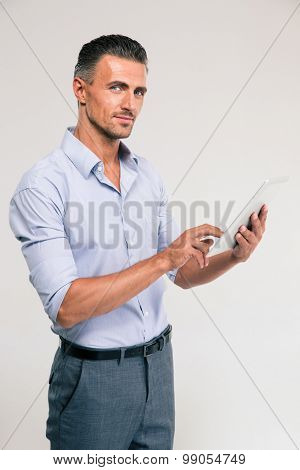 Portrait of a happy businessman using tablet computer and looking at camera isolated on a white background