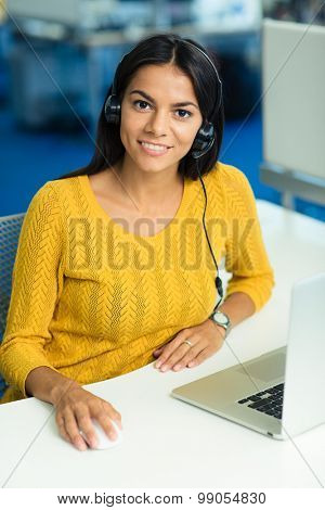Cheerful businesswoman in sweater sitting at her workplace with headphones in office and looking at camera