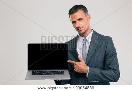 Portrait of a handsome businessman showing blank laptop computer screen isolated on a white background