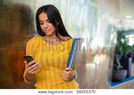 Portrait of a beautiful businesswoman using smartphone in hallway