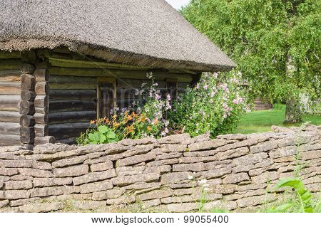 Rural Log Cabin With Garden Flowers And Limestone Fence On Foreground
