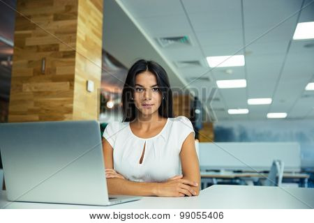 Portrait of a charming businesswoman sitting at the table in modern office