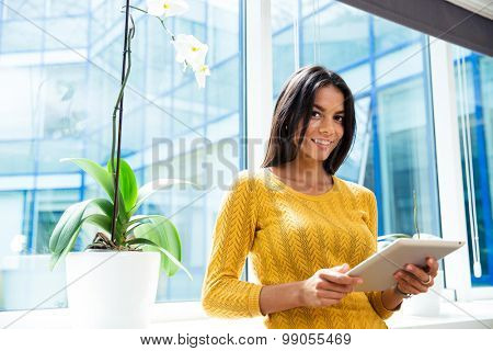 Portrait of a smiling casual businesswoman standing with tablet computer in office near window and looking at camera