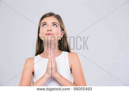 Portrait of attractive female teenager praying isolated on a white background. Looking up
