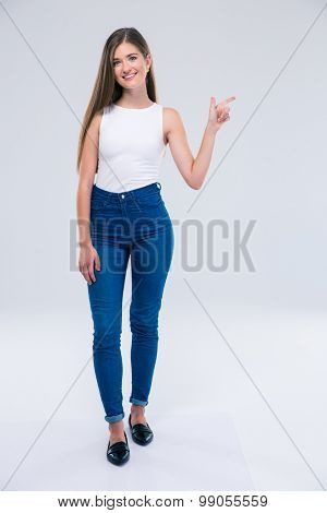 Full length portrait of a cheerful female teenager pointing finger away isolated on a white background. Looking at camera