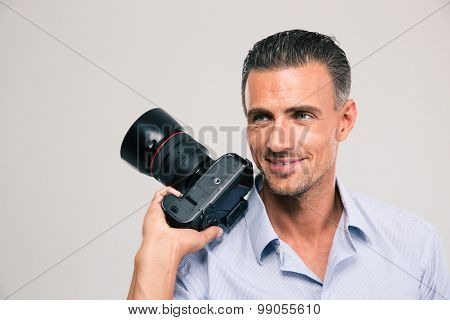 Portrait of a smiling handsome man holding camera and looking away isolated on a white background