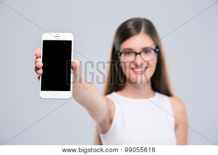 Portrait of a happy female teenager in glasses showing blank smartphone screen isolated on a white background. Focus on smartphone