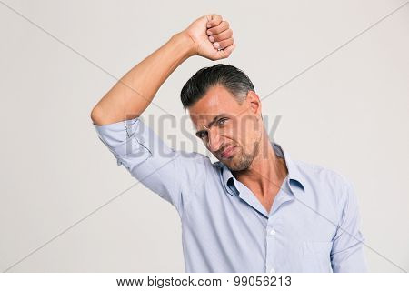 Man smelling sniffing his armpit something smells bad foul odor isolated on a white background