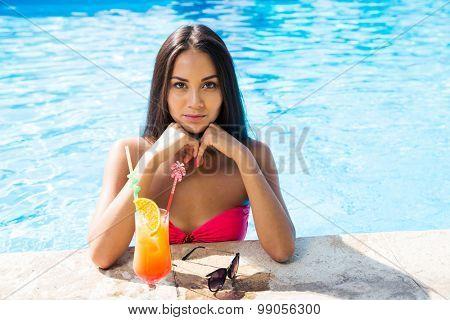 Portrait of a woman sunbathing in swim pool outdoors