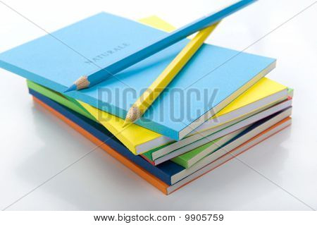 two colored pencils under the stack of books