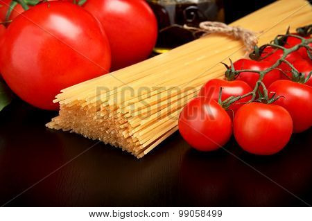 Long Pasta Raw Isolated On Black With Tomatoes And Olive Oil