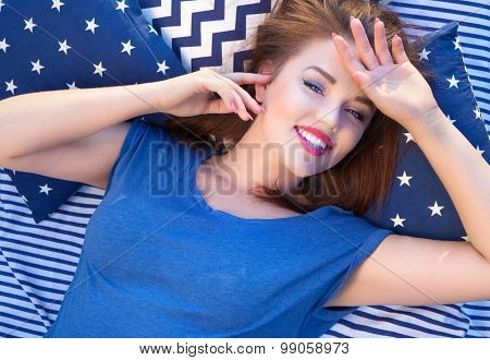 Happy beautiful young  woman lying in bed