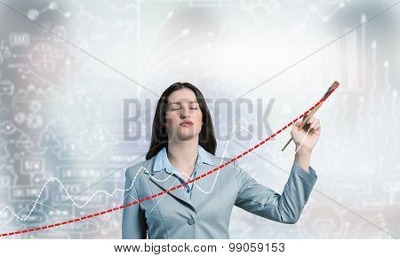 Young businesswoman drawing increasing graph with paint brush