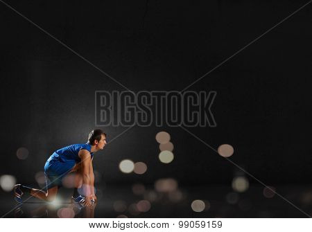 Young man athlete standing in start pose