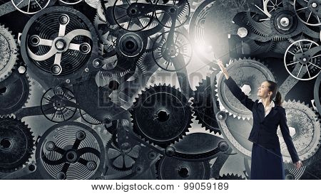 Young businesswoman reaching hand to touch gears mechanism