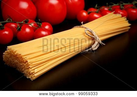 Long Pasta Raw Isolated On Black Table With Tomatoes